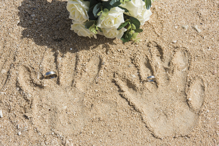 Abstract beach wedding concept with handprints and rings in sand with bouquet Archivio Fotografico