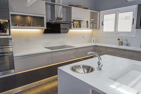 Wystrój wnętrz przedstawiający nowoczesną kuchnię z szafkami w salonie luksusowych apartamentów Zdjęcie Seryjne