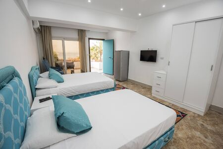 Twin beds in bedroom of luxury apartment showing interior design with tropical sea view and window Banco de Imagens
