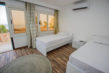 Twin beds in bedroom of luxury hotel room apartment showing interior design with tropical sea view and window