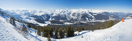 Panoramic view across snow covered alpine mountain range in alps on blue sky background Reklamní fotografie