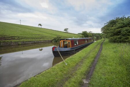 Narrowboat moored up in English rural countryside scenery on British waterway canal during overcast cloudy day 版權商用圖片