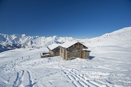 Panoramic view of snow covered mountains in an alpine ski resort with stone building on remote slope