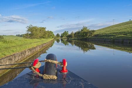 View of an English rural countryside scenery from bow of narrowboat on British waterway canal
