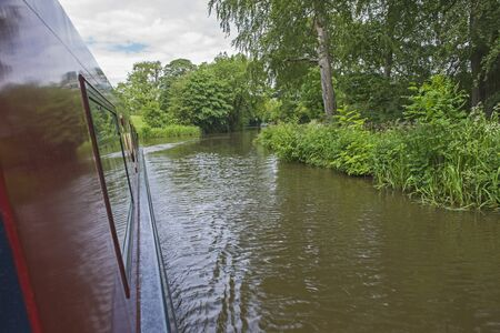 View from narrowboat traveling through English rural countryside scenery on British tree lined waterway canal 版權商用圖片