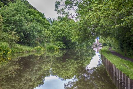 Landscape view of English rural countryside scenery on British waterway canal lined with trees 版權商用圖片