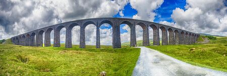 View of a large old Victorian railway viaduct across valley in rural countryside scenery panorama