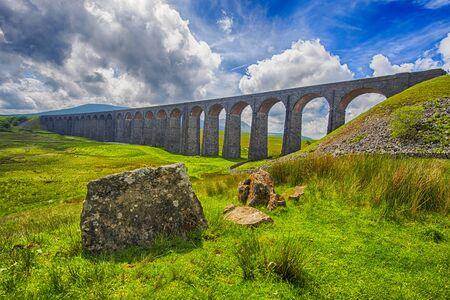 View of a large old Victorian railway viaduct across valley in rural countryside scenery panorama with stone wall