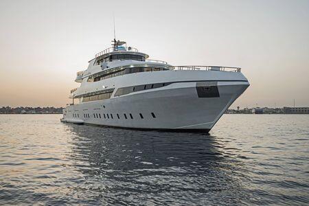 Eine luxuriöse private Motoryacht unterwegs auf tropischem Meer mit Bugwelle bei Sonnenuntergang