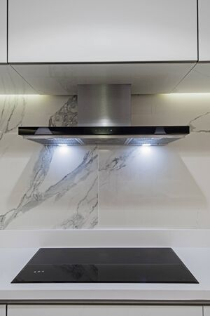 Interior design decor showing modern kitchen cooker hob appliance with extractor fan in luxury apartment showroom