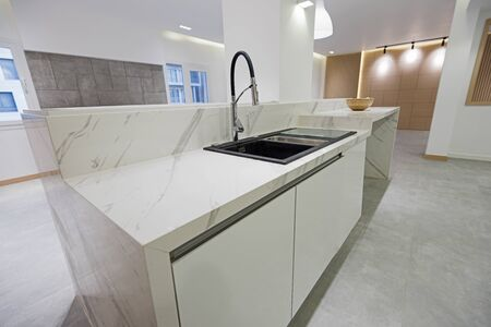 Interior design decor showing modern kitchen with sink and island in luxury apartment showroom