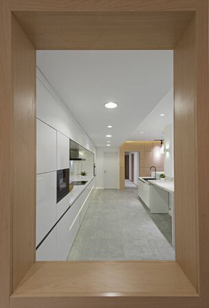 Interior design decor showing modern kitchen with cupboards in luxury apartment showroom through window frame 写真素材