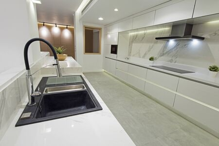 Interior design decor showing modern kitchen with cupboards and island in luxury apartment showroom 写真素材