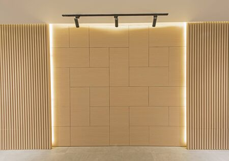 Closeup of blank tiled wall cladding framed with strip lighting making background wallpaper