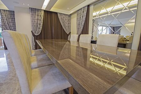 Living room area in luxury apartment show home showing interior design decor furnishing with open plan dining table area