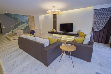 Living room lounge area in luxury apartment show home showing open plan interior design decor furnishing