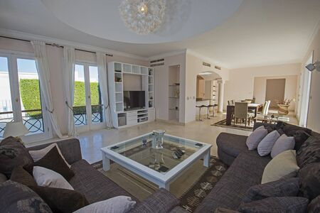 Living room lounge in luxury villa show home showing interior design decor furnishing and open plan kitchen dining area