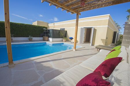 Luxury villa show home in tropical summer holiday resort with outdoor swimming pool and sun chairs