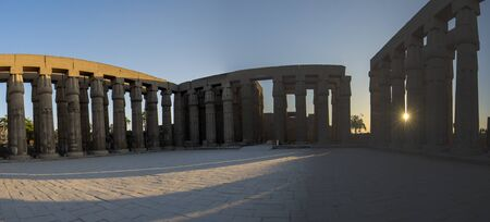 Columns with hieroglyphic carvings around courtyard in ancient egyptian Luxor Temple at sunset Banco de Imagens