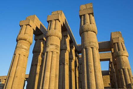 Columns with hieroglyphic carvings in ancient egyptian Luxor Temple at sunset