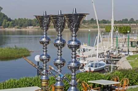 Traditional Egyptian shisha water pipe with felluca sailing boats in rural countryside setting along the river Nile in Egypt