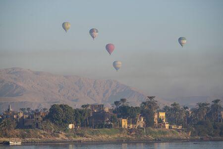 Panoramablick auf die ländliche Landschaft mit Blick auf den großen Nil in einer trockenen Umgebung mit Luxor-Westufer und fliegenden Heißluftballons
