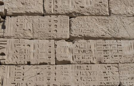 Hieroglypic carvings on wall at the ancient egyptian temple of Medinat Habu in Luxor Banco de Imagens