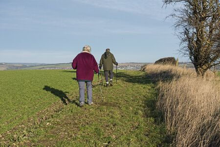 Two elderly people walking ramblers on remote country lane road up a hill in rural countryside landscape