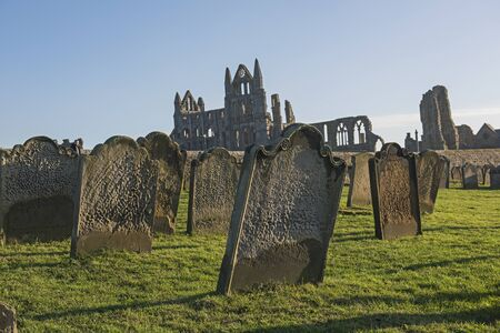 Remains of an ancient english abbey ruins with gothic architecture in rural countryside landscape and cemetary