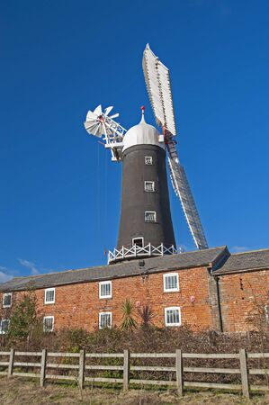Old traditional working windmill in rural countryside landscape with blue sky background