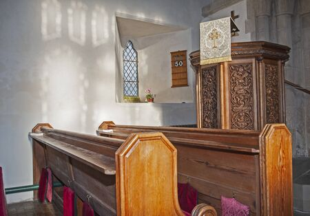 Interior of small medieval village church with pew seating and altar