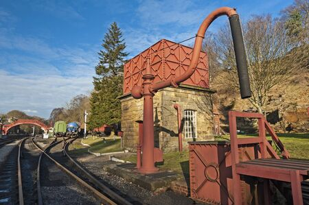 Old traditional railway water steam engine water pump and rolling stock on a siding