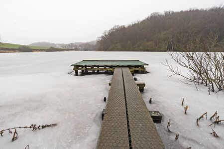 Small jetty pontoon protruding on a frozen snow covered lake surrounded by woodland