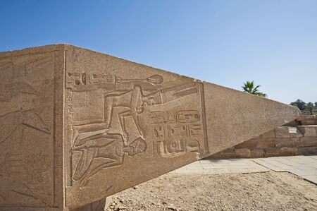 Large ancient egyptian obelisk lying at the temple of Karnak in Luxor with hieroglyphic carvings on blue sky background Banque d'images