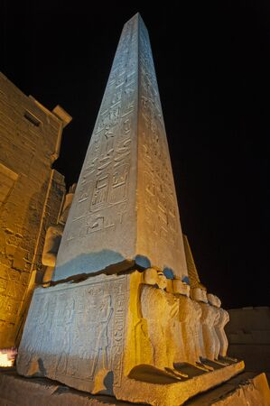 Large tall ancient egyptian obelisk at the temple of Luxor with hieroglyphic carvings lit up in night