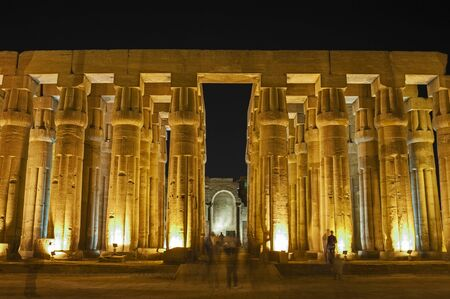 Hieroglypic carvings on large columns at the ancient egyptian Luxor temple lit up in night