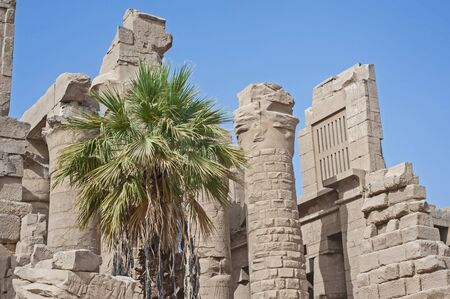 Outdoor external large stone columns at temple of Karnak in Luxor Egypt with blue sky background