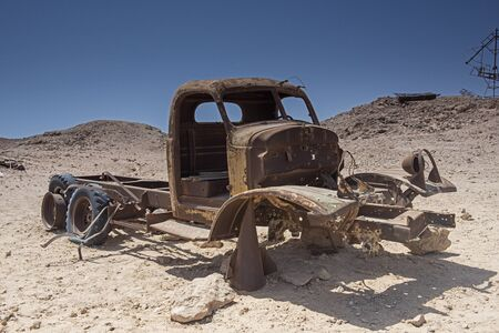 Remains of a rusty old abandoned derelict truck left in the desert to decay Stock Photo