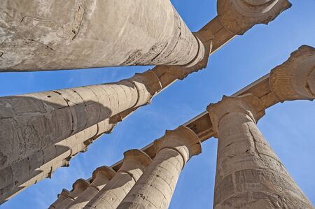 Hieroglypic carvings on columns at the ancient egyptian Luxor temple with blue sky background