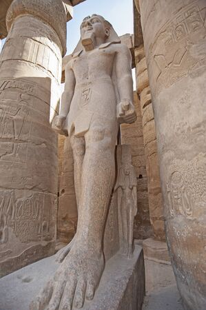 Large statue and hieroglypic carvings of Ramses II at the ancient egyptian Luxor temple with columns Reklamní fotografie