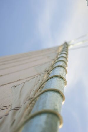 Abstract view of wooden sailing boat mast with shallow depth of field selective focus showing rigging on blue sky background