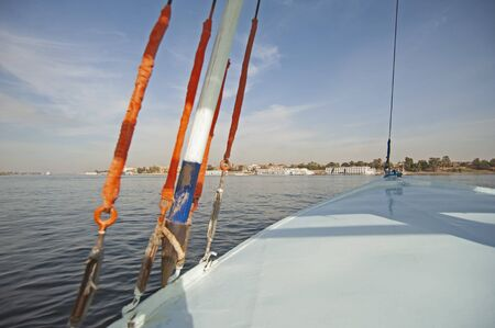View across large wide river Nile in Egypt to riverbank through rural countryside landscape from sailing boat with rigging Stok Fotoğraf