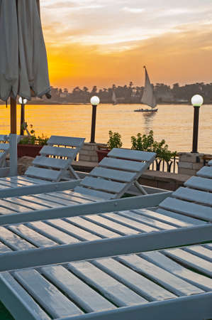 Landscape view of traditional egyptian felluca sailing boat on river Nile at dusk sunset from hotel with sunbeds