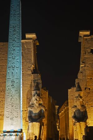 Large statue and obelisk at entrance pylon to ancient egyptian Luxor Temple lit up during night Foto de archivo