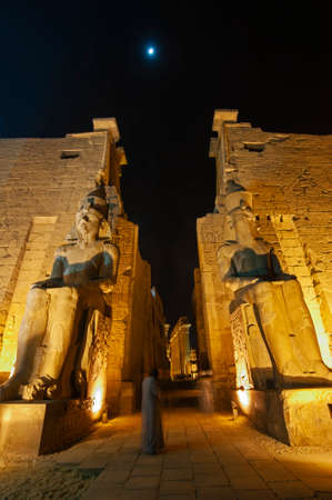 Large statues of Ramses II at entrance pylon to ancient egyptian Luxor Temple lit up during night
