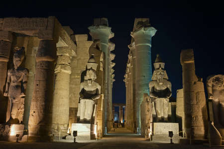 Large statues of Ramses II with columns in hypostyle hall at ancient egyptian Luxor Temple lit up during night