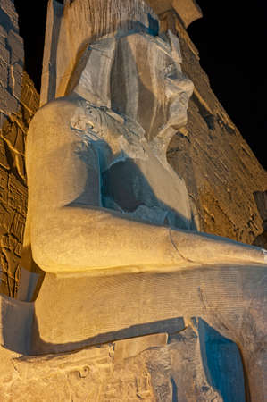 Large statue of Ramses II at entrance pylon to ancient egyptian Luxor Temple lit up during night Banque d'images
