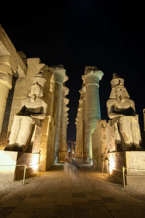 Large columns in hypostyle hall at ancient egyptian Luxor Temple lit up during night