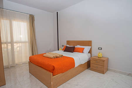 Interior design decor furnishing of luxury show home bedroom showing furniture and double bed with balcony