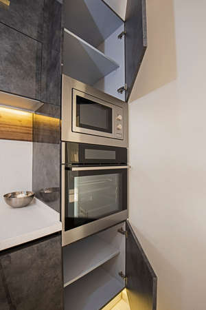 Interior design decor showing modern kitchen cooker oven with cupboards in luxury apartment showroom